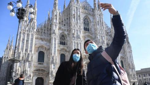 turistas-con-mascarillas-ante-el-duomo-de-milan